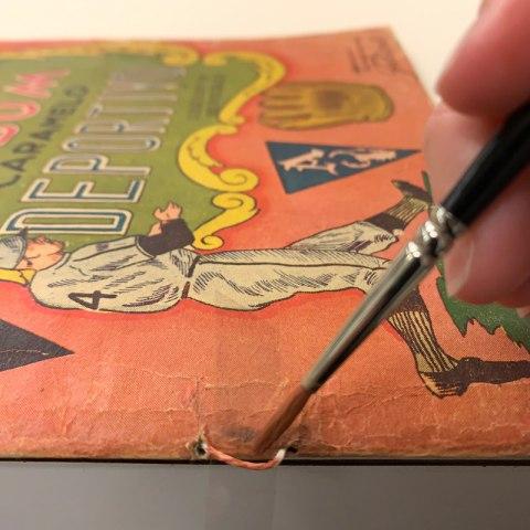 Conservator sews linen thread along the spine of the Caramelo Deportivo album