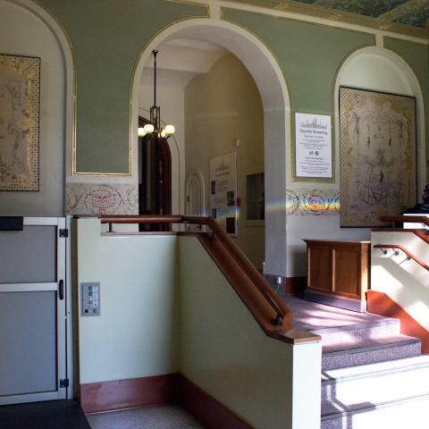 Color photo of a room that has stairs leading up to it (approx. four) and a lift to the left. The room is sunlit and has white arches and green paint.