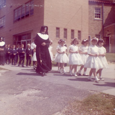 Photo two nuns walk with a line of students. The girls, at the front of the line, wear white dresses and have headbands on. The boys, in the back of the line, wear blue suits. They're on a sidewalk outside a building.