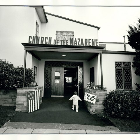 """A young child is shown walking into church with sign """"Church of the Nazarene."""" An American flag and """"Polling Place"""" sign hand in the foreground."""