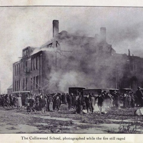 """An black and white image of a building surrounded by smoke. People gather around it, many in hats and winter jackets. The full caption at the bottom of the picture reads """"The Collinwood School, photographed while the fire still raged"""""""