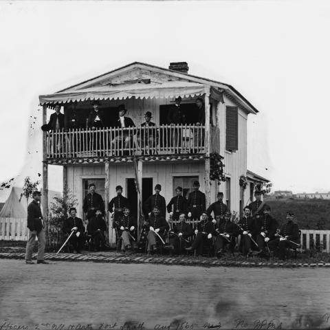 Black and white photo of small, two-story house with balcony and porch. Approx. 20 soldiers in uniform sit and stand outside the house.