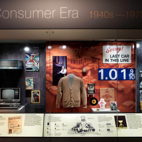 """Photo of display case that says """"Consumer Era 1940s-1970s"""" featuring historic objects. One sign on display says """"Sorry! Last car in this line."""""""