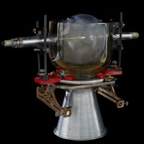 A scientific device sits against a black background. A thick shield of glass obscures the details of the device. It sits on a silver pedestal.