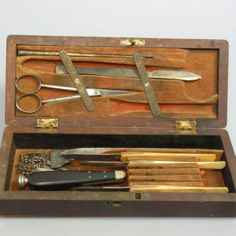 A wooden box filled with various tools that include blades and scissors