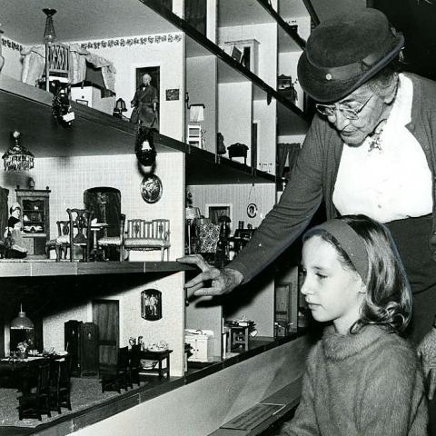 In black and white photo, a young girl looks at doll house with guidance of an older woman