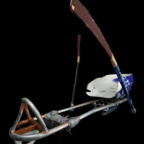 A structure used as a sled. It has metal bars to support the legs and feet and a seat. Two wooden staffs that appear to be shortened hockey sticks are attached to either side.