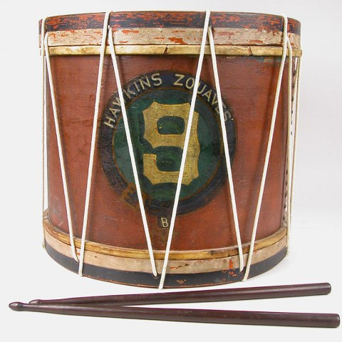 A chestnut-colored drum with a pair of drumsticks