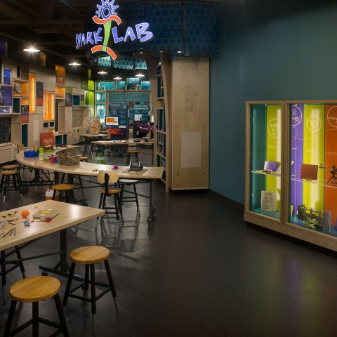 """Photo of a large space with high ceilings. Tables in the center include space for inventing. Cabinets on both sides contain cases with museum objects, including what looks like a guitar. Above, in lights, is a sign that says """"Spark Lab."""""""