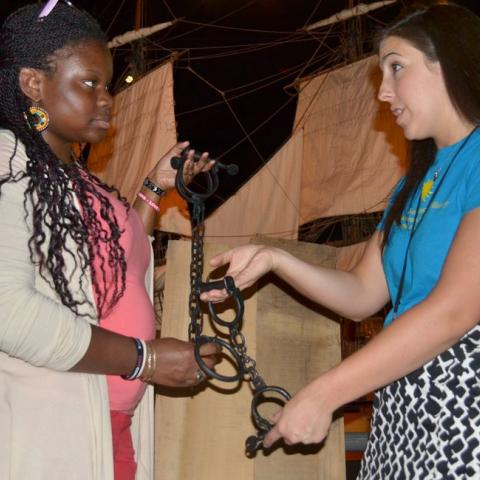 two educators hold model slave shackles in front of a model ship