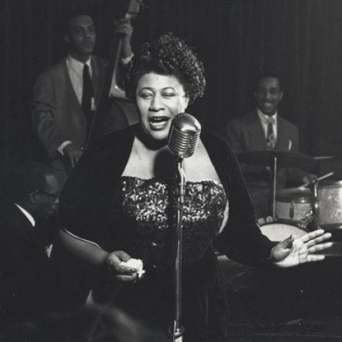 In a black and white photo, a woman stands behind a microphone and sings in a dark room. A jazz band is behind her, and they are smiling.