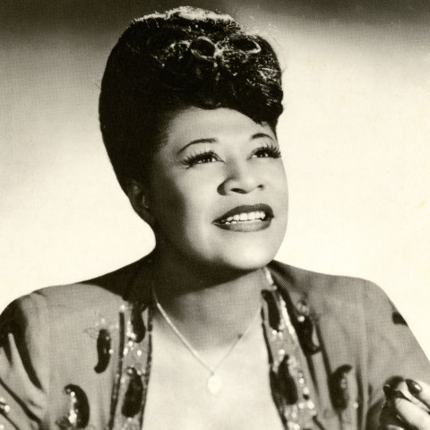 a photograph of Ella Fitzgerald. She looks up and away from the camera. She is smiling and rests on a number of records spread out on the table in front of her.