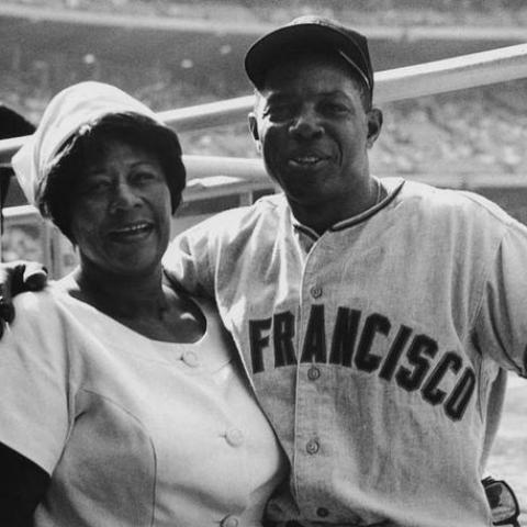 Ella in white suit and hat with baseball player