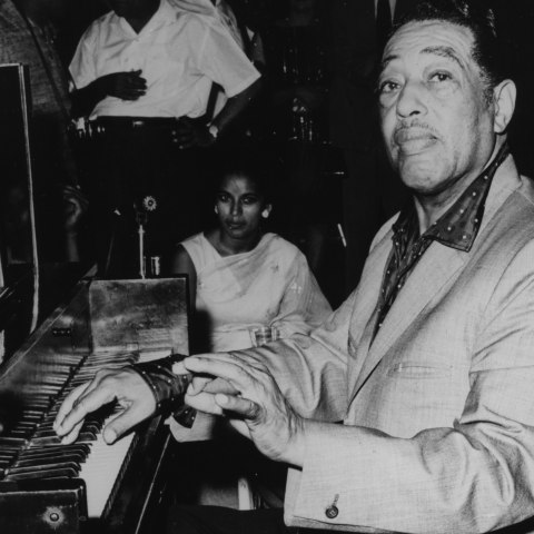 Black and white photo of Ellington at piano. Ellington turns slightly to face camera, his right hand on the keys.