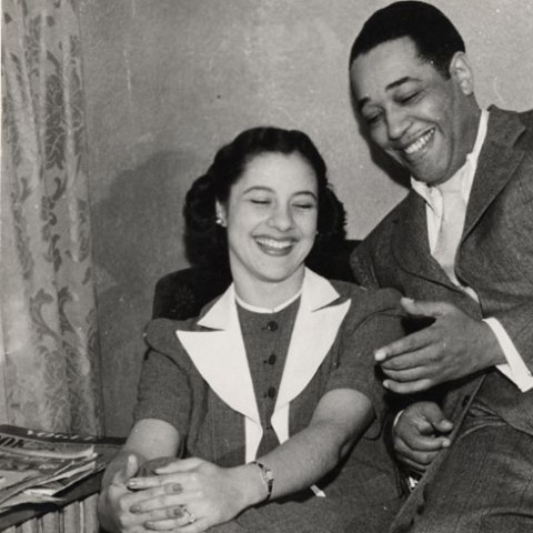 Detail of image: Black and white snapshot. A woman sits in a chair, her legs crossed and her hands on knee. She smiles, eyes closed and mouth open to show her teeth. She wears a smart suit with white collar. The man balances on one of the arms of the chair, gesturing toward her, also with a smile. He wears a suit and black/white shoes.