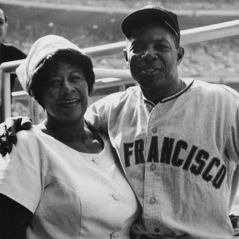 Woman in white suit and hat poses with man in baseball uniform and hat. Big smiles. In background, baseball stadium.