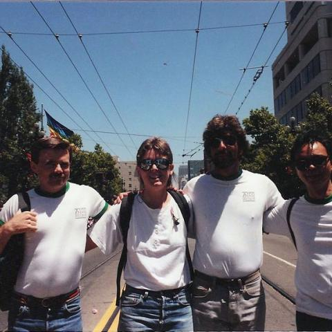 Color photograph of four people in which shirts, arms inter-linked, walking on or standing in street during daytime, parade crowd in background