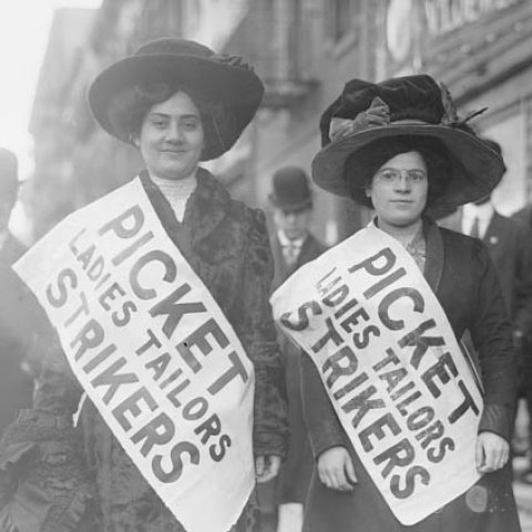 "Black and white photo of two women looking at camera. Large hats. They wear sashes/signs that says ""Picket ladies tailors strikes."" Street scene."