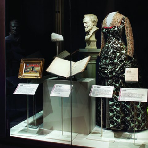 Museum case containing woman's gown, marble bust, nurse's cap, and small painting. Each item has a label.