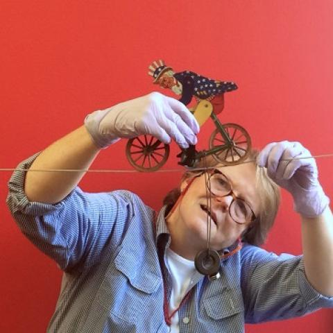 A museum employee wears glove and holds an Uncle Sam toy