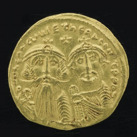 A coin with two bearded men on it along with text and a small cross