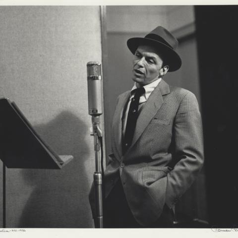Frank Sinatra in hat and tie stands at microphone with music stand in front of him, mouth slightly open