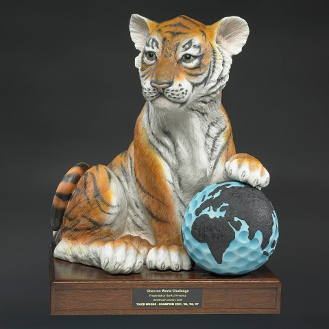 An award on a short wooden base of a young tiger with its paw on what appears to be a golf ball painted light blue with the world on it.