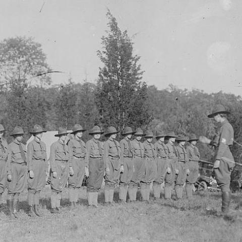 Black and white photo of women in uniforms (pants, ties, hats, boots) lined up looking at a woman who appears to be in charge.