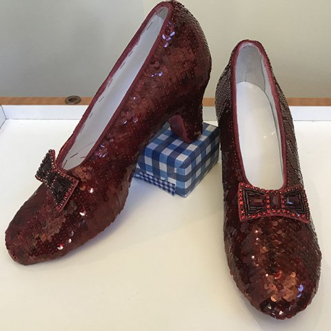 A pair of replica ruby slippers sit inside of a display case. They are positioned so that the toes are pointed slightly away from one another, and one of the shoes has its heel places on a small box covered in blue gingham wrapping paper.