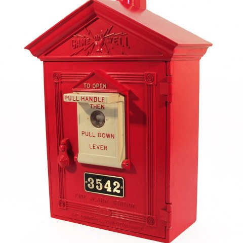 A red box shaped like a fire house station with a pull handle. The box is decorated with the company logo of Gamewell, complete with a hand gripping bolts of electricity.