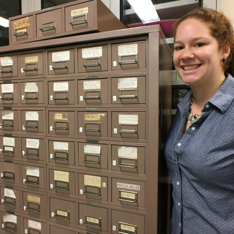 Young woman with curly red hair and a blue button-down shirt smiles, posing beside a filing cabinet, which is beige with white labels and metal handles.