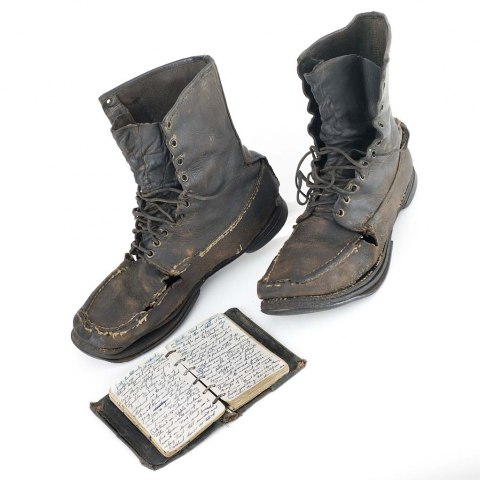 A pair of dark leather books that are higher than ankle-length. They lace up the front. They have seen wear, as some of the seams look worn and the soles look like they're coming apart. On the ground in front of the shoes is a notebook. It looks to be made of dark leather and has rings like a modern binder, with pages covered in dark cursive.