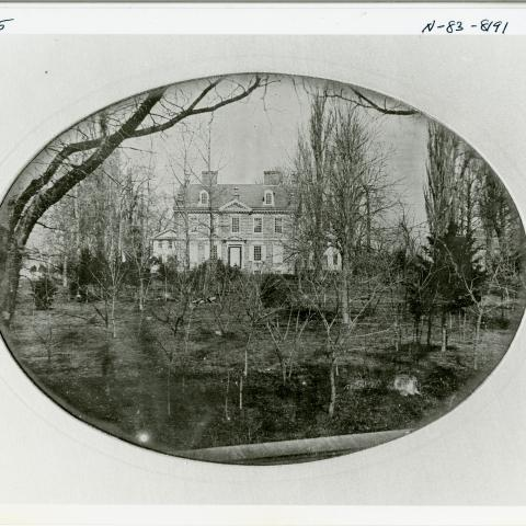 Black and white photo of building surrounded by trees