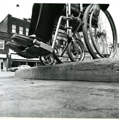 Black and white photo from street level looking up at two feet in wheel chair and a high curb.