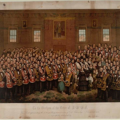 Color print with image of a group of many men posing in a room with older gentlemen in middle along with a few women in six or seven children. The room has high ceilings and four windows along with a portrait. They are all wearing sashes and aprons that match.