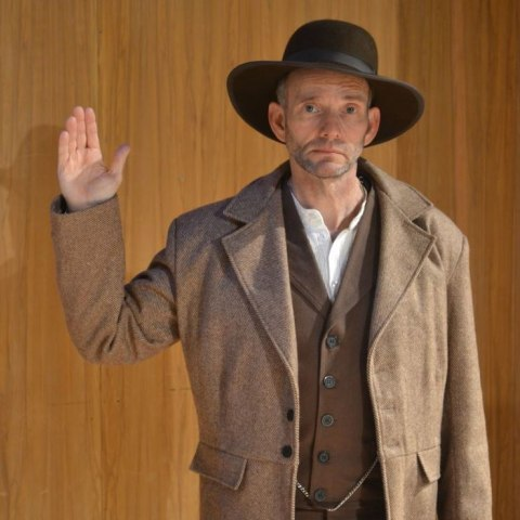 Photo of man wearing a black hat and brown coat. He faces camera with an anxious expression, his right hand raised as if swearing an oath.