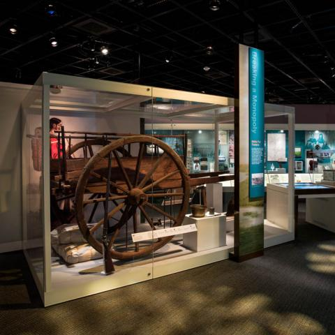 A photograph of the exhibition's Merchant Era section, featuring a red river cart