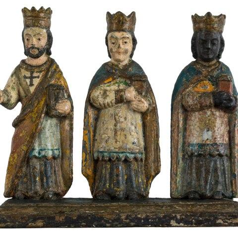 """Small statuette of the Three Kings, or """"Reyes Magos."""" The three figures are joined together by a shared base. Though they have different expressions and garb, they all wear crowns and are posed carrying a small gift."""