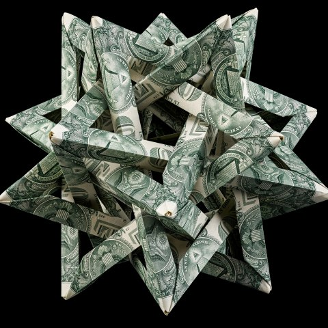 A sculpture made from one dollar bill(s). It is complex with interwoven triangles that give it a spiked sort of appearance.