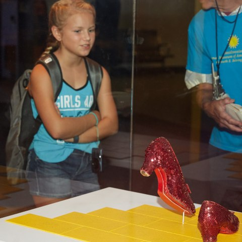A little girl admires the Ruby Slippers in a display case