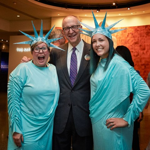 Photograph of Skorton welcoming visitors at the opening of the new wing. He is joined by two museum staffers dressed in Statue of Liberty costumes.