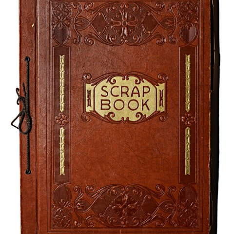 Cover of Leopoldo Martinez's red leather scrapbook. The embroidered book has features the text: Scrap Book.