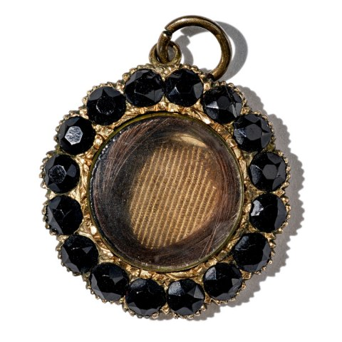 Gold locket with black onyx stones along its border and brown hair embedded in the center under glass.