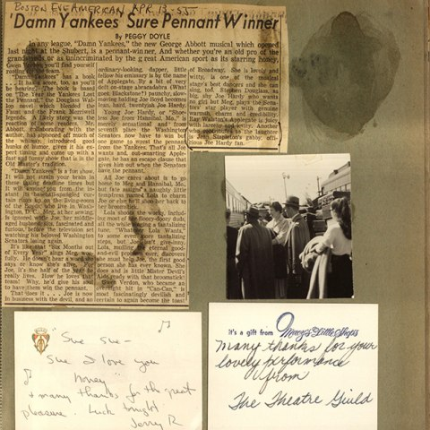 Newspaper clippings, white cards with handwritten text, and a photograph on old, faded paper. There are dark streaks on some of the clippings and the page.