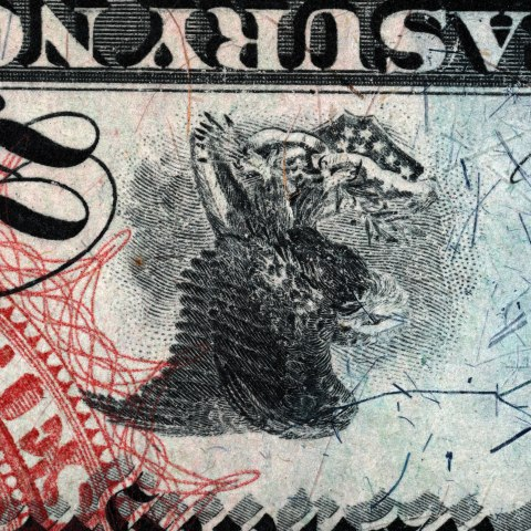 A portion of a piece of currency. It depicts a bird upside wen surrounded by stamp-like decorations in green, red and black. There are many scratch marks on the right side of the frame.