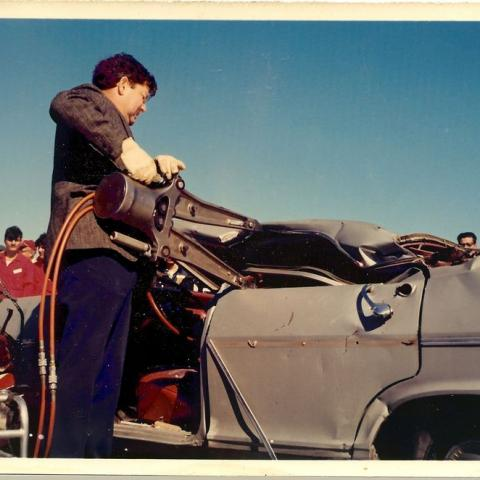 Photo of man demonstrating the jaws of life on wrecked car