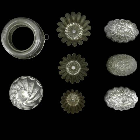 1930s entrée salad molds, metallic containers with decorative designs on black background