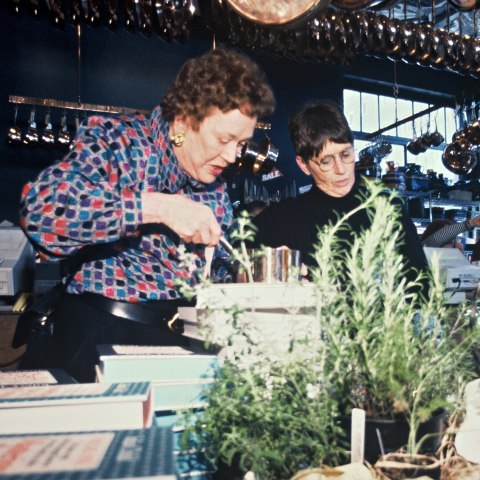 Color photo of two women in a kitchen surrounded by cookbooks, rosemary plants, dishes, plates, and more. One is holding a pan or pot and peering into it, while the other, by her side, does something that is hard to see due to a rosemary plant.