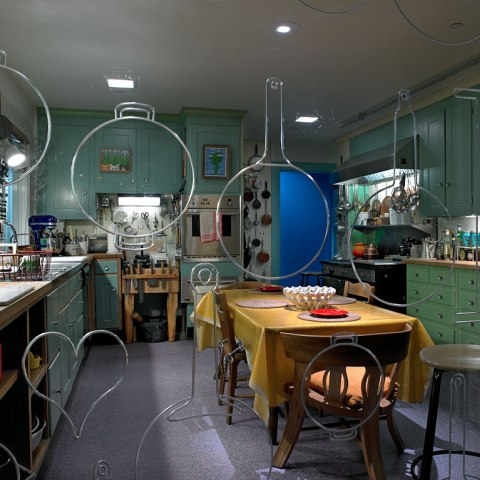 Photo of a kitchen with light blue cabinets, a large rectangular dining table with marigold tablecloth, and lots of pots and pans.