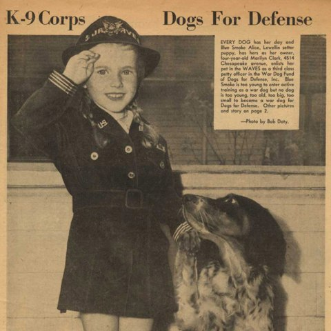 Scan of newspaper-style image. A little girl in uniform with big smile gives a salute and so does her spotted dog, who looks up at her.
